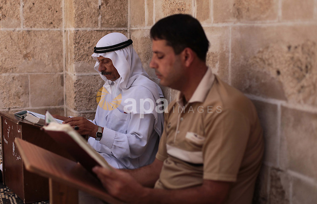 Palestinian muslims read the holy Qur'an at mosque in Gaza city, on June 30, 2014. Muslims around the world refrain from eating, drinking and sexual intercourse from dawn till dusk during Ramadan, the holiest month in the Islamic calendar. Photo by Ashraf Amra