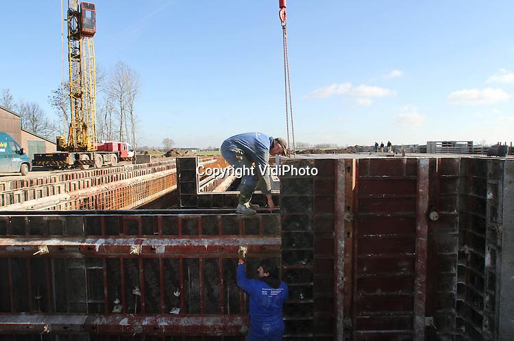 Foto: VidiPhoto..HERVELD - Personeel  van aannemer Jan van Wees uit het Gelderse Rijswijk dinsdag aan het werk in een bouwput van maatschap Peek in Herveld. De Betuwse melkveehouder laat een moderne veestal bouwen met 139 boxen en twee melkrobots. Onder de stal komt een mestput van 3000 kuub met electrische mixers. In juni moet de koeienstal gereeed zijn. De koeien van Peek staan altijd binnen..