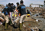 Volunteers pull a body from the wreckage in Banda Aceh, Indonesia on January 10, 2005.  The asian tsunami killed over 100,000 people in Indonesia.  (photo by Khampha Bouaphanh)
