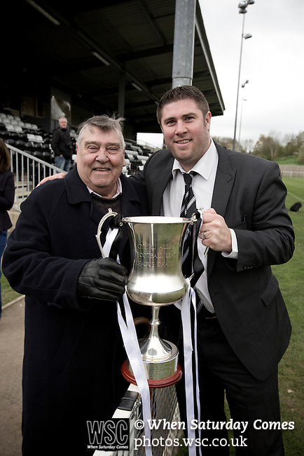 Cefn Druids AFC 1 Buckley Town 0, 12/04/2014. The Rock, Cymru Alliance league. Home team manager Huw Griffiths (right) with his father and the league trophy at The Rock, Rhosymedre, home to Cefn Druids AFC, after the club's final home game of the season against Buckley Town (in yellow) in the Cymru Alliance league. Druids, reputedly the oldest football club in Wales, won the Alliance league the previous week and were awarded the trophy after the Buckley Town match, which they won by 1 goal to nil, watched by a crowd of 246. The Cymru Alliance was the second tier of Welsh football based in north and mid Wales, promotion from which led directly into the Welsh Premier League. Photo by Colin McPherson.