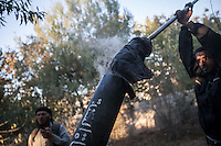 In this Tuesday, Oct. 08, 2013 photo, opposition fighters reload a mortar launcher during an attack over Wadi Al-Deef military post at the frontline in Maraat Al-Nouman in the Idlib province countryside of Syria. (AP/Photo)