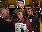 A group of demonstrators protest President-elect Trump's resistance to divesting himself of his business holdings in the lobby of Trump Tower in New York, NY, USA December 15, 2016. <br /> Credit: Albin Lohr-Jones / Pool via CNP