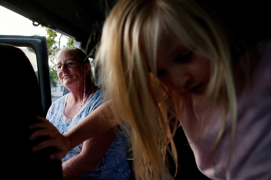 "Ventura, California, August 3, 2010 - A portrait of Robin Ferguson and her granddaughter, Katie Eldridge, 5, in Ms. Ferguson's van, where she has called home for the last year. Ms. Ferguson lived in a home with her 2 sons, daughter-in-law and newborn granddaughter up until 2007, when she and one of her sons lost their jobs. They were unable to keep up with the rent and were forced to move to the back patio of her parent's home. ""It was so cold during the winter because it was just a roof over the porch,"" says Ms. Ferguson. Last year she says a neighbor called the City's code enforcement who gave her seven hours to move everything out. She moved into her van where she has lived since. Ms. Ferguson has a job - she works as a noon aide at Will Rogers Elementary - but she says she does not make enough to rent a home or apartment. Just this month, after three years of waiting, she was finally approved for low income housing assistance. She says that she is so happy that she will be off of the streets. ""I am grateful - just being able to feel like a complete person, self sufficient, not having to depend on some else to have a safe place to be."" ."