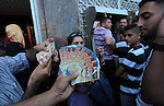 Employees paid by the Palestinian Authority show their salaries after withdrew from an ATM as others wait to receive their salaries outside a bank after a scuffle with employees appointed by Hamas since 2007, in Gaza City on June 11, 2014. Gaza's banks reopened Wednesday after being closed for six days by Hamas forces, an official said, in a dispute that is the first challenge to a new Palestinian unity government. The PA has so far refused to pay Hamas's 50,000 civil servants, who are not registered as its employees because they were appointed after the Islamist movement ousted bitter rivals Fatah -- which dominates the PLO -- from Gaza in 2007. Photo by Ashraf Amra
