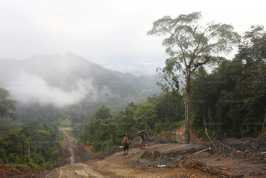 August 2012: Penan natives watch as their homes are threatened yet again by so-called development. Petronas Sabah-Sarawak gas pipeline is being excavated across the Borneo rainforest ravaging native areas. Close to Long Adang, Belaga district, Sarawak, Borneo<br />