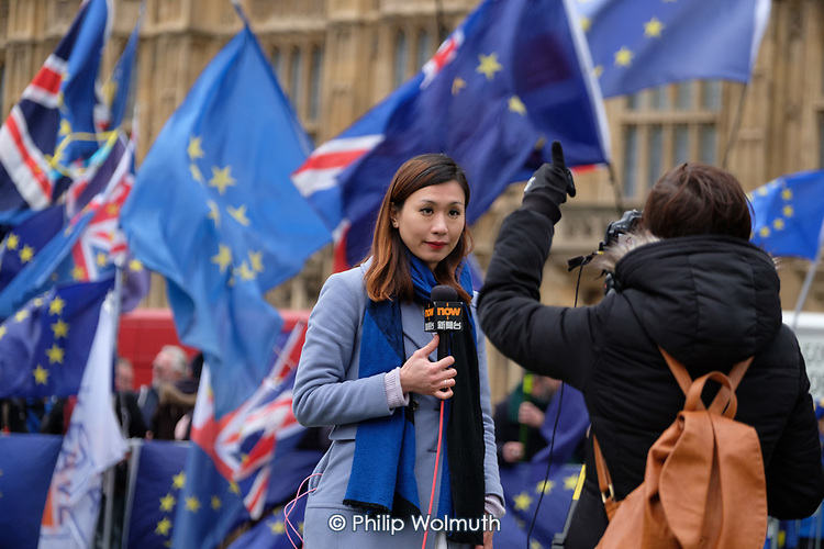 NOW online news presenter on College Green, outside the Houses of Parliament, on the day MPs voted decisively to reject Theresa May's withdrawal deal with the EU.  Westminster, London.