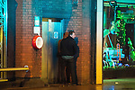 "© Joel Goodman - 07973 332324 . 17/12/2016 . Manchester , UK . A man is illuminated by the blue lights of a police van as he is caught urinating in a doorway on Deansgate . Revellers out in Manchester City Centre overnight during "" Mad Friday "" , named for being one of the busiest nights of the year for the emergency services in the UK . Photo credit : Joel Goodman"