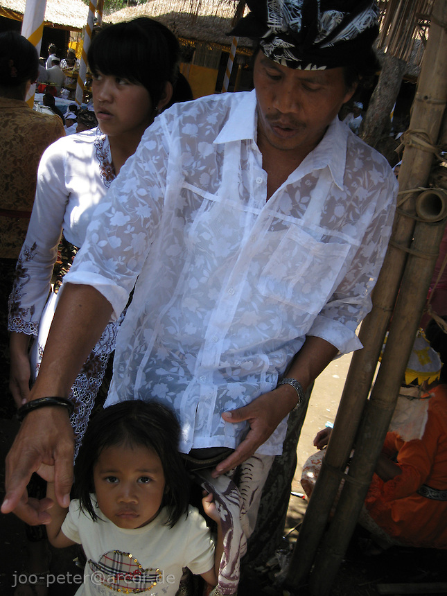 father and child pass through the crowd while teeth filing ceremony in Bentuyung village Bali, archipelago Indonesia, 2010
