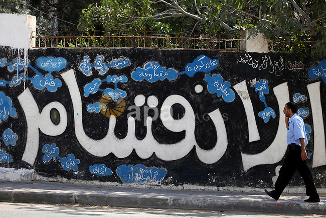 """A Palestinian man walks past a graffiti reading in Arabic ''Division'' in Gaza City, on September 17, 2017, after Hamas announced it had agreed to steps toward resolving a decade-long split with the Fatah movement and was ready to hold elections. Hamas said it had agreed to key demands made by Fatah: dissolving the so-called """"administrative committee"""", while saying it was ready for elections and negotiations toward a unity government. Photo by Mohammed Asad"""