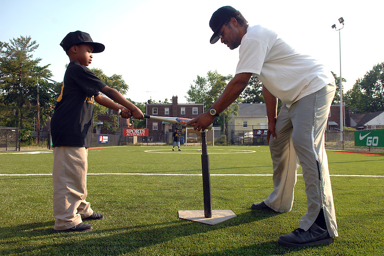 Michael Lancaster, 8, gets instructions on hitting from Ronald Barnes, during teeball practice at the Boys and Girls Club of Washington, in Anacostia.
