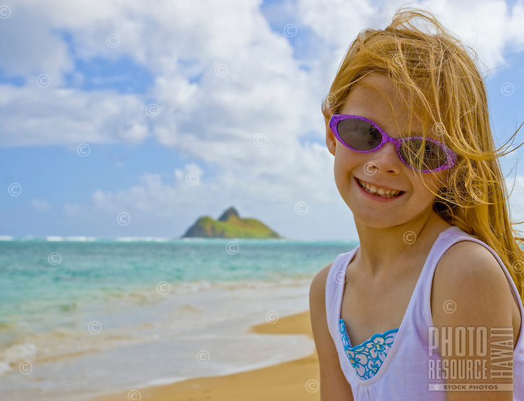 A young girl takes a break from beach fun at Lanikai.  The Mokulua Islands are in the background