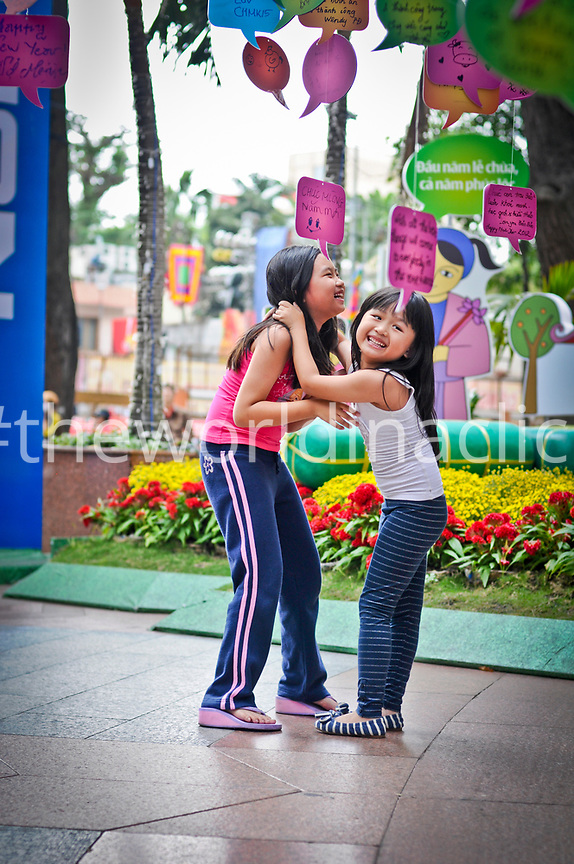 VIETNAM, Ho Chi Minh, two girls laughting and hugging under paper decoorations