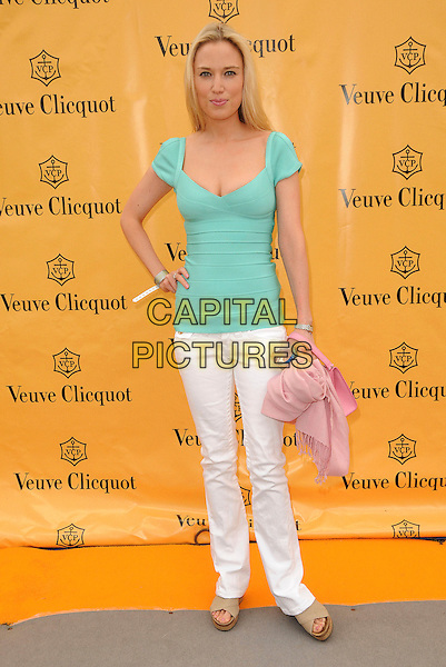 IMOGEN LLOYD WEBBER .Veuve Cliquot Gold Cup Polo, Cowdray Park, England, UK, July 19th 2009..full length green top hand on hip white trousers jeans Herve leger bandage tight fitting beige sandals open toe shoes  pink bag.CAP/CAS.©Bob Cass/Capital Pictures