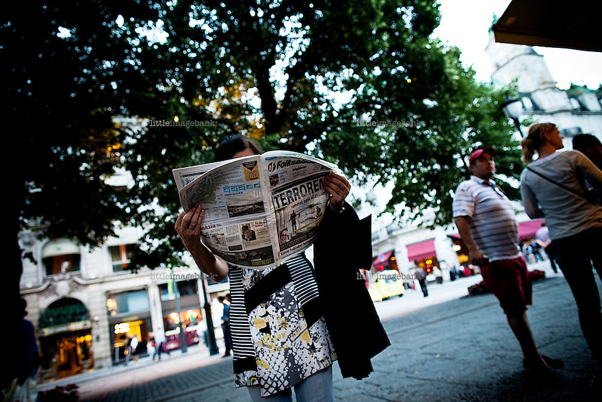 Oslo, Norway, 23.07.2011. A lady reads horrific news. Oslo awakes to shocking messages of the total bodycount after yesterdays massacre. A total of 91 persons were killed in the massacre in Utøya right outside Oslo. Seven of those died when a car bomb was detonated outside the main government biuilding in the heart of Oslo, friday 22. of July. Foto: Christopher Olssøn.