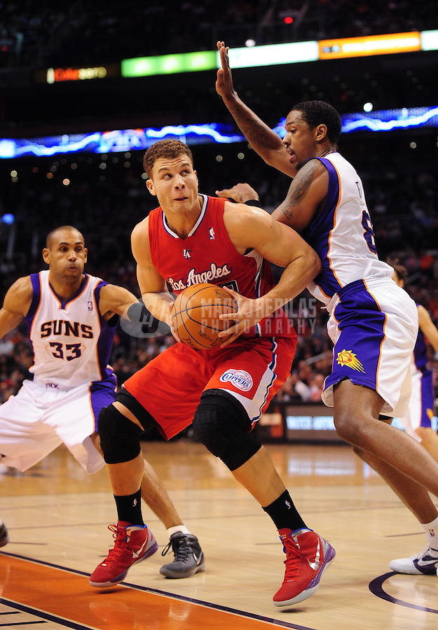 Mar. 2, 2012; Phoenix, AZ, USA; Los Angeles Clippers forward Blake Griffin (left) controls the ball against Phoenix Suns center Channing Frye at the US Airways Center. The Suns defeated the Clippers 81-78. Mandatory Credit: Mark J. Rebilas-USA TODAY Sports
