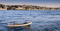 Travel Photography; World Cultures. A father sailing on the Bosphorus Strait with his son in Istanbul, Turkey. A patriotic family flying their red Turkish flag as they go fishing.