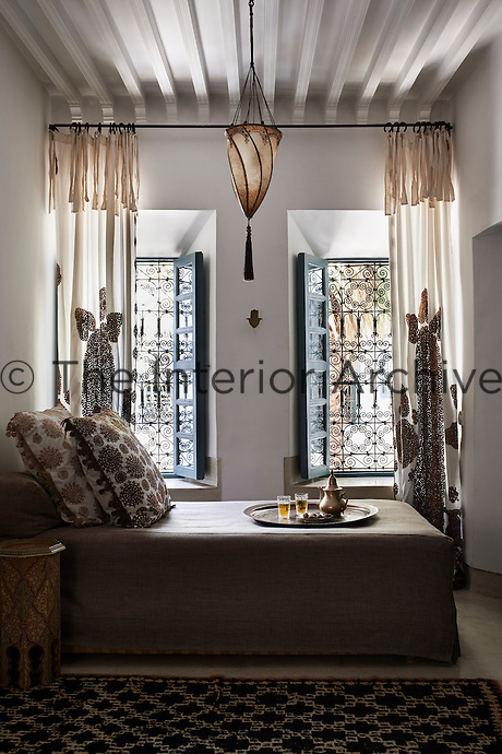 The restful bedroom is decorated in neutral and taupe colours. The full length curtains hang from a metal curtain rod either side of the decorative shuttered windows.