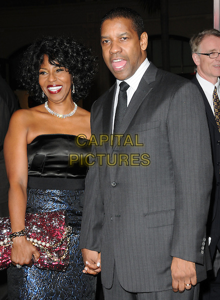 "PAULETTA & DENZEL WASHINGTON .at Alcon Entertainment's L.A. Premiere of ""The Book of Eli"" held at The Chinese Theatre in Hollywood, California, USA,  January 11th 2010..half length black and blue shiny dress grey gray suit tie married couple husband wife clutch bag pink beaded red jewelled jewel encrusted pattern patterned holding hands .CAP/RKE/DVS.©DVS/RockinExposures/Capital Pictures."