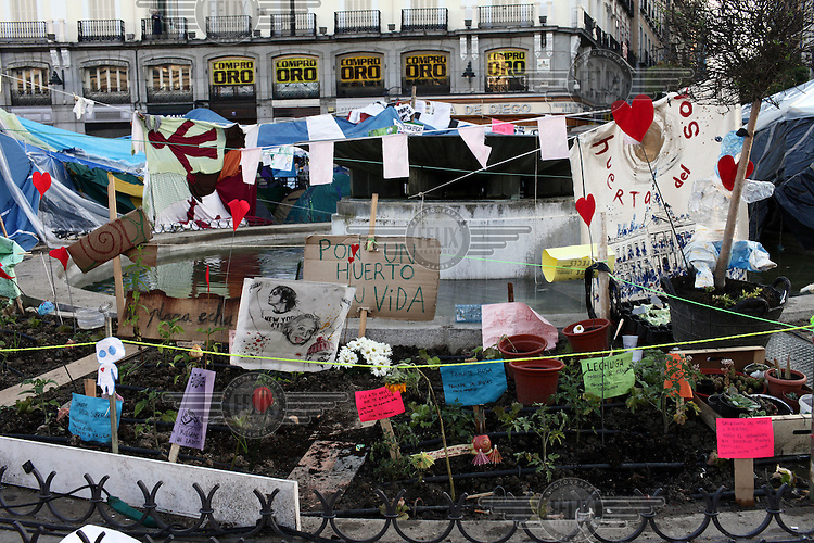 A garden planted by the 'indignados' decorated with signs, paintings and banners. In May 2012, following a worsening financial crisis and a deepening recession in Spain, thousands of people started to gather in Spanish cities to protest against austerity, the global financial system, high unemplyment rate (Spain's is the highest rate in Europe) and the lack of opportunities. The protest movement has become known as 'los indignados' (the indignant ones).