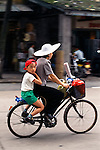 mother and boy riding by on bicycle, city street in Guangzhou (Canton), China, Asia