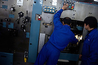 Plant workers adjust a new printing press in the new Bible printing facility for the Amity Printing Company in Nanjing, China. ..The Amity Printing Company is the only company allowed to publish Christian Bibles in China and, with this new printing facility scheduled to open in May 2008, is the world's largest producer of Bibles.  The Amity Foundation, the Chinese charity which oversees the Amity Printing Company, was founded in 1985 with the express purpose of promoting education, health, social welfare, and rural development in China.