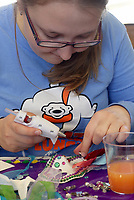 NWA Democrat-Gazette/DAVID GOTTSCHALK Olga Brazhkina, a junior at the University of Arkansas, uses a glue gun to place items on her mask Monday, February 12, 2018, during the Beads and Bling It's a Mardi Gras Thing in the Arkansas Union International Connections Lounge on the campus in Fayetteville. The celebration, hosted by University Programs, offered King Cake, mask decorating, trivia and other activities.