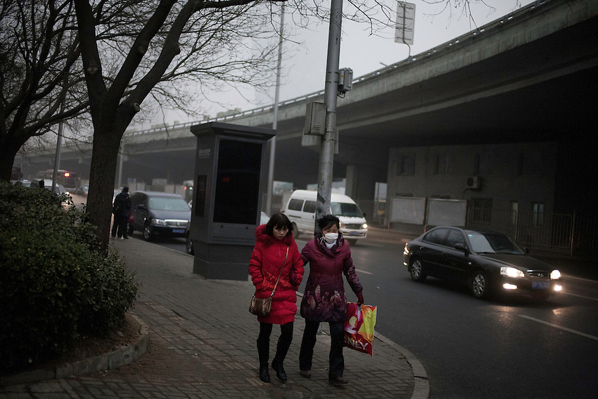 17 March 2012; 4&deg;C, Around 17h30 - Beijing.<br /> Two chinese women are walking near the third ring road of the Guomao district. One of them wears a mask against the strong pollution that covers Beijing this 17 March 2012. Almost 250 flights were cancelled at the Beijing Capital Airport and several highways closed. Particles mesured by the American embassy indicates &quot;Hazardous&quot;...