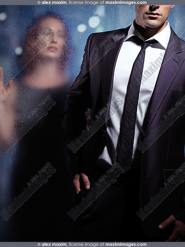 Artistic dramatic portrait of a young man walking away leaving a woman behind wet glass door outside