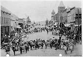 Main street in Telluride with a 65-mule pack train, each carrying 2 each 100-foot coils of cable for the Nellie Mine.  All of the coils are connected in a 13,000-foot length.  A large crowd of onlookers has gathered to see this.  If the date is accurate, it is somewhat strange that there are no Independence Day decorations in sight.<br /> Telluride, CO  7/3/1897