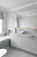 An ensuite bathroom with grey marble flooring and splashbacks. Understated pattern has been introduced in the blind and along the bath