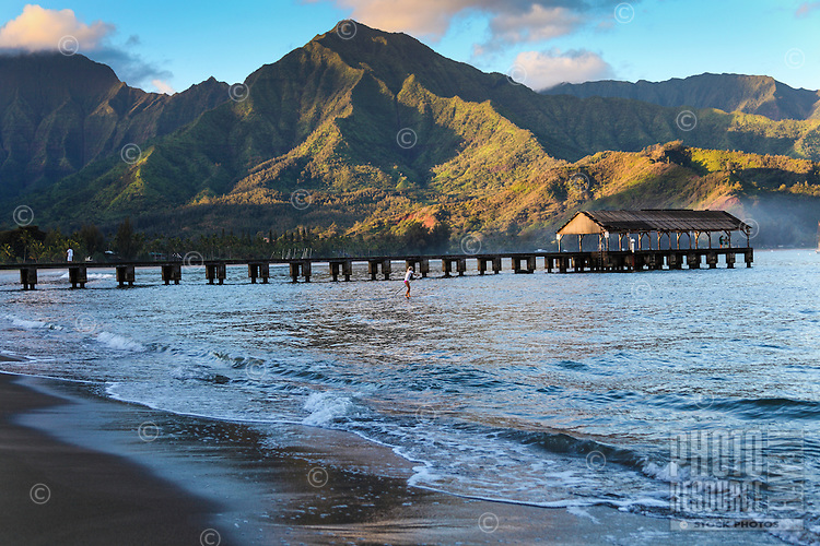 A standup paddler in the morning light at Hanalei Bay, with a fisherman and others on Hanalei Pier in the distance, North Kaua'i.