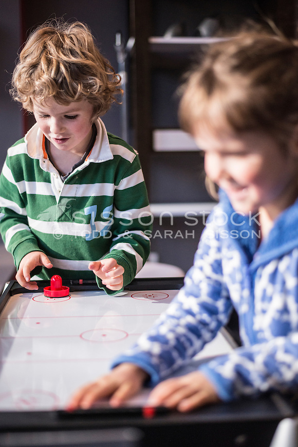 Children (5 and 6 years) playing table hockey, New Zealand - stock photo, canvas, fine art print