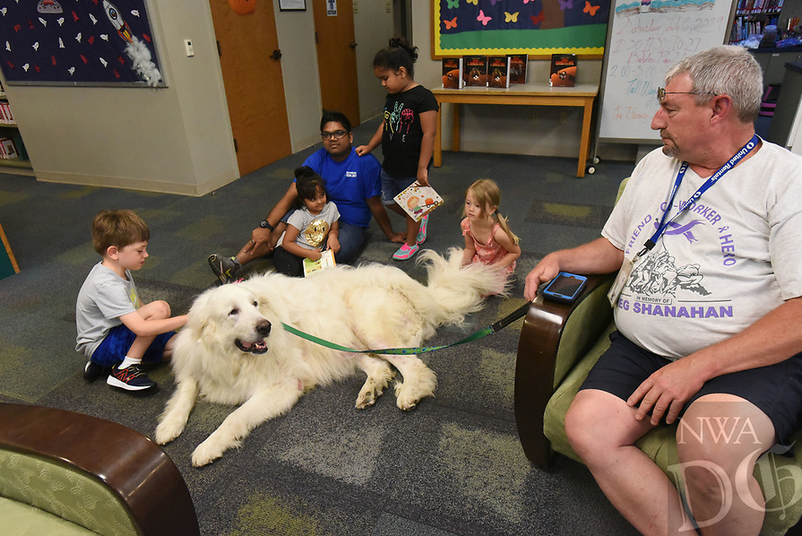 NWA Democrat-Gazette/FLIP PUTTHOFF <br /> FURRY READING PAL<br /> Larry Gramling (right) of Centerton watches his dog, Obi, a certified therapy dog, be the center of attention Saturday July 6 2019 at the Rogers Public Library. Gramling brought the great pyrenees dog to the library for children to pet and read books to Obi. Gramling and Obi make regular appearances at libraries, shelters and other locales including Northwest Arkansas Regional Airport. Obi lets passengers stroke his soft fur and helps soothe passengers who may be stressed.