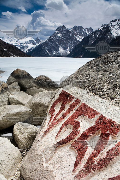 Markings on rocks next to frozen Green Dragon Lake beneath mountains in the west of the province.