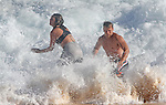 A couple finds Sandy Beach in Hawaii during high-tide a little rough as waves break close to shore.