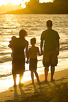A family with two young children enjoy a beautiful sunrise on Kailua Beach.