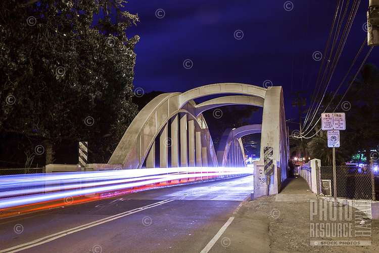 Light trails from moving traffic on the Anahulu Stream Bridge at night in Haleiwa, North Shore, O'ahu.
