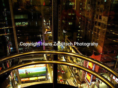 View from a modern glaselevator at Kowloons Nathan Road by night.