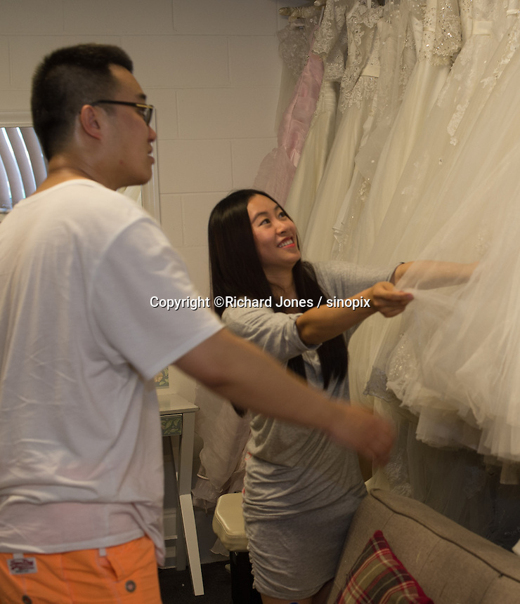 Zing,  and his bride, both from China, prepare for their pre-wedding photos, that will be taken in Cornwall, at JR Studio in East London, UK, 19th July 2016.