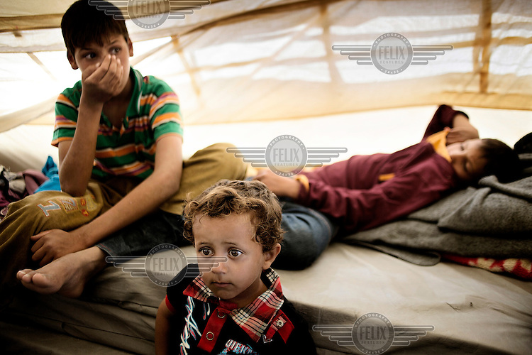 Three children in a tent at the Zaatari Refugee Camp. They are all survivors of the chemical weapons attack on the Damascus suburb of Ghouta on 21 August 2013. When the chemical attack took place their father covered the children with wet blankets to protect them from the gas. His fast thinking probably saved their lives, but they were all still suffering symptoms when, several days later, they arrived at the camp. They have difficulties breathing, and suffer headaches, dizziness, stinging eyes and vomiting.  Approximately two million people have fled the conflict in Syria. At least 130,000 of them live in Zaatari Refugee Camp, although it was designed to house 60,000, and a further 2,000 people arrive each day.