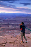 Tourist taking pictures high above the Colorado River from Dead Horse Point, Dead Horse Point State Park, UTAH