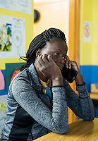 Mary Kuanen takes a moment to call family back in Sudan during a break from work at Blessed Sacrament Catholic School in Denver, Colorado, Friday, October 21, 2016. Kuanen a refugee from Sudan moved to Denver 11 years ago with her husband and children. Five years ago her husband was murdered in a mistaken identity gang shooting. <br /> <br /> Photo by Matt Nager
