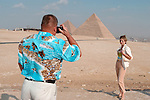 CAIRO - NOVEMBER 30, 2004 : Foreign tourists take pictures in front of the 5000 years old Giza pyramids in Cairo, on November 30, 2004. Situated high on a desert plateau overlooking sprawling Cairo, Giza is the most visited tourist site in Egypt ,with the Sphinx and the 481ft high great Pyramid. Tourism has been on the decline in Egypt following a series of terrorist attacks targeting foreign tourists. (Photo by Jean-Marc Giboux)