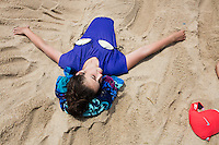 Amelie Lachance-Soulard, 16, of Ottawa, Canada, lay buried under sand sculptures of mermaid tails at Herring Cove Beach in the Cape Cod National Seashore outside of Provincetown, Mass., USA, on Fri., July 1, 2016. Portions of the parking lot have been closed after land eroded during storms earlier this year. This was the girls' first visit to the area.