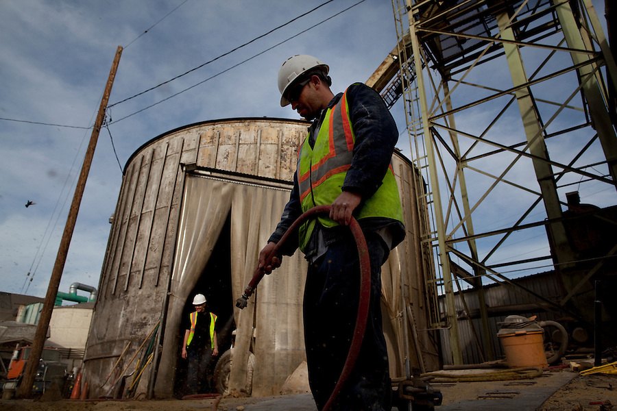 Los Angeles, California, March 1, 2010 - Emilio Razo, right, uses an air hose to clean the transport lines along the rails for the next freight load of sugar beet pellets destined for Korea and Japan at the Los Angeles Harbor Grain Terminal. Demand for U.S. products is spiking in Asia, thanks to a weak dollar and quicker economic recovery. However, decline in U.S. consumption has left exports short of a good exit strategy. In 2009, imports fell 28%. This has created a bottleneck for exports, which need the shipping containers to move product overseas. ...