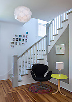 An entrance hall with a staircase with a grey painted banister and treads and a wooden floor. A black Arne Jacobsen Swan chair and a simple side table with a lamp, stand in one corner.