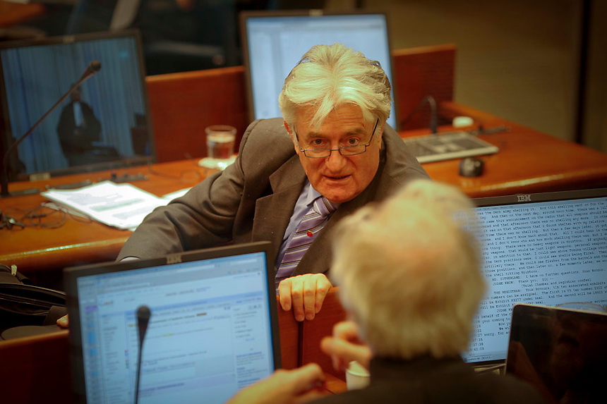 Former Bosnian Serb leader Radovan Karadzic talks to a member of his defence team during a trial in a courtroom of the International Criminal Tribunal (ICTY) for the former Yugoslavia September 19, 2011. Karadzic, who rejects responsibility for some of Europe's worst atrocities since World War Two, faces 11 charges against him, including two of genocide, for his actions during the Bosnian War of 1992-95, which pitted Serbs against Muslims and Croats. Karadzic is detained at the ICTY's Detention Unit located within a Dutch prison complex in the Scheveningen neighbourhood of The Hague.     REUTERS/Damir Sagolj (NETHERLANDS)
