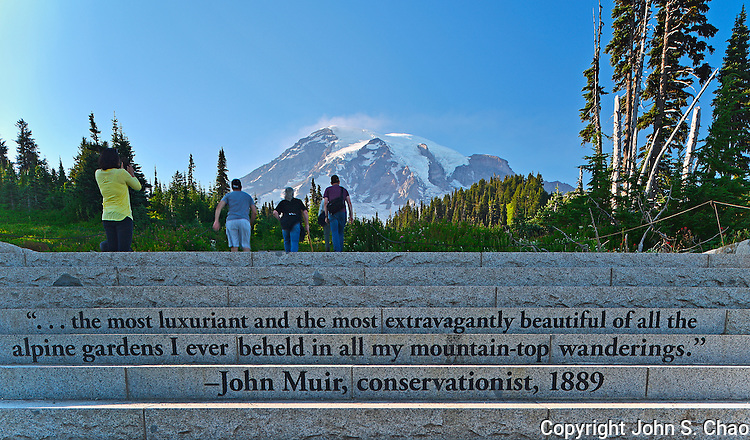 Visitors walk towards Mount Rainier, above words of John Muir inscribed into granite steps, at the Paradise area of Mount Rainier National Park, Washington State
