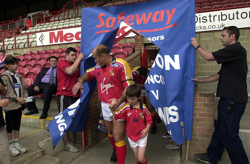 Photo. Richard Lane.London Broncos v Widnes. Tetley's Super League..24-08-2002.Broncos captain, Jason Hetherington leads the team out with mascot, Calum Smith.