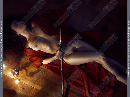 Beautiful nude woman with a bamboo flute in undone red kimono lying on the floor in dim dramatic candle light
